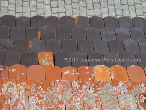 Looking down from the wall--roofing tiles and sidewalk. Very quilty.